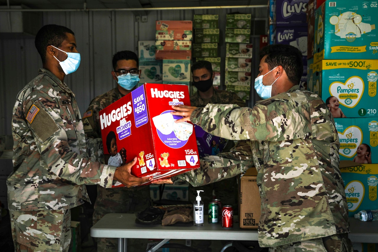 One soldier hands another soldier a box of diapers.