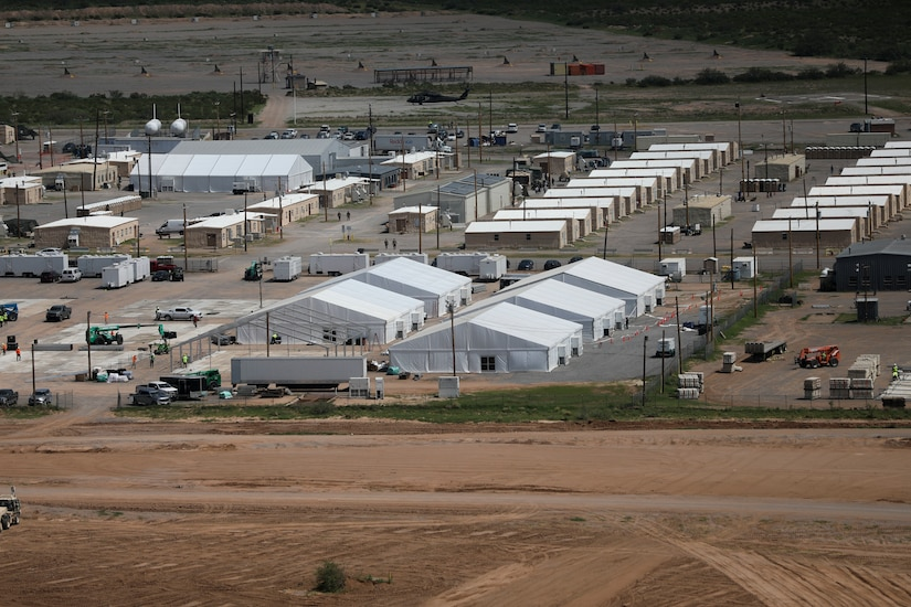 A grid of white temporary structures is spread out near an airfield.