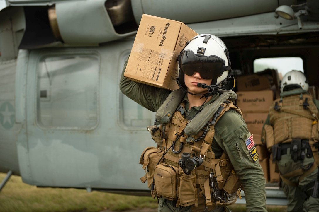 Hospital Corpsman 3rd Class Jace Borowiak carries a box of food from an MH-60S Sea Hawk helicopter during a humanitarian aid mission supporting the U.S. Agency for International Development (USAID), Aug. 25.