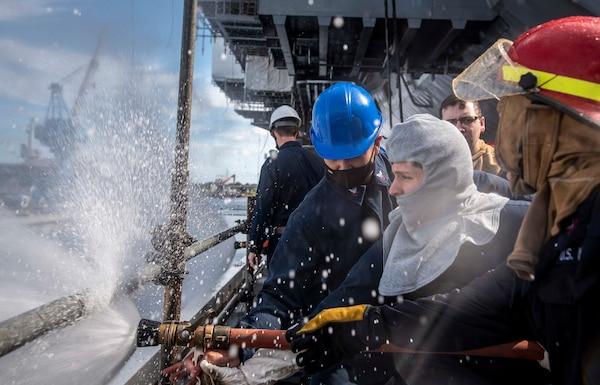 Sailors discharge a hose during a fire drill aboard the aircraft carrier USS George H. W. Bush (CVN 77).