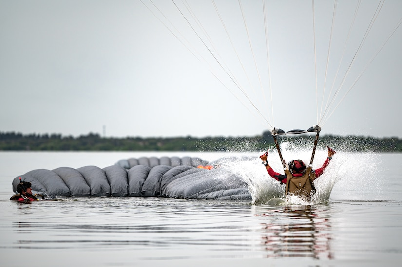 Photo of Airman landing in the water with a parachute