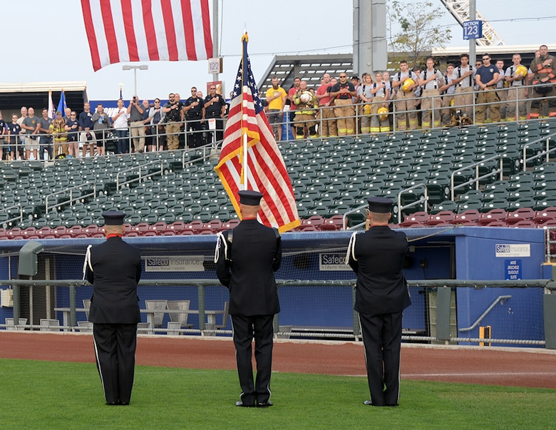 Honor guard fireman holding the U.S. flag in front of a crowd of civilians; firemen and policemen with their hands over their hearts