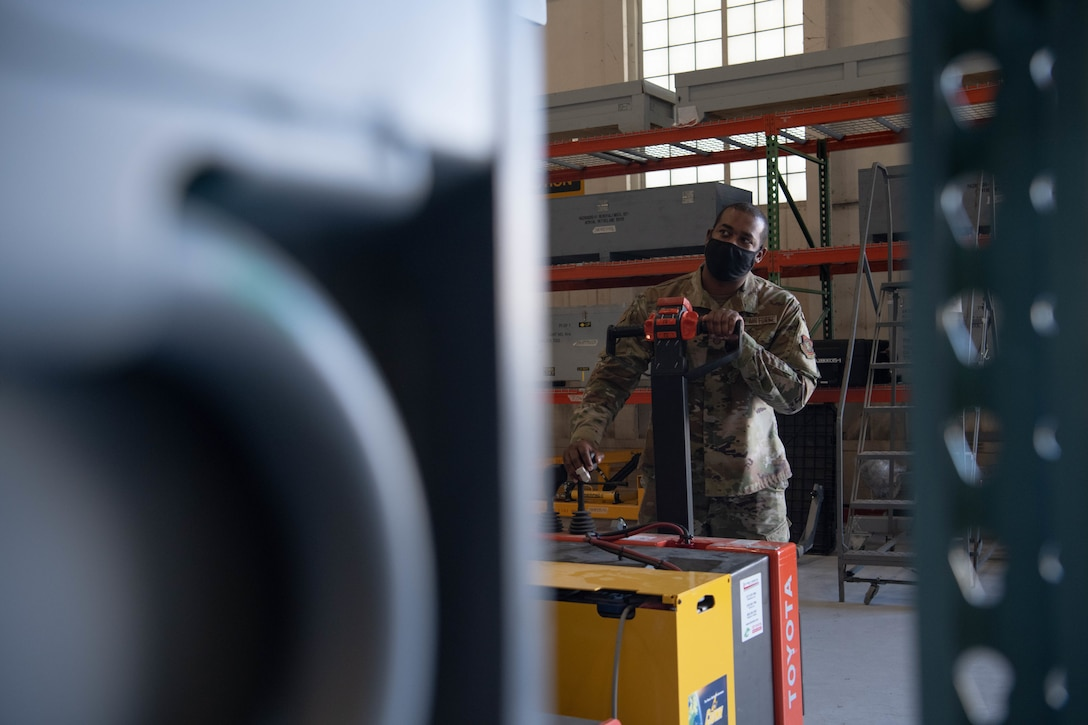 Tech. Sgt. Lorenzo Latney, 22nd Aircraft Maintenance Squadron KC-135 equipment custodian, utilizes a pallet jack to store a toolkit Aug. 24, 2021, at McConnell Air Force Base, Kansas. In addition to increased storage, the consolidated tool kit now has a streamlined system of locating tools to increase efficiency and minimize time spent on tool retrieval. (U.S. Air Force photo by Senior Airman Marc Garcia)