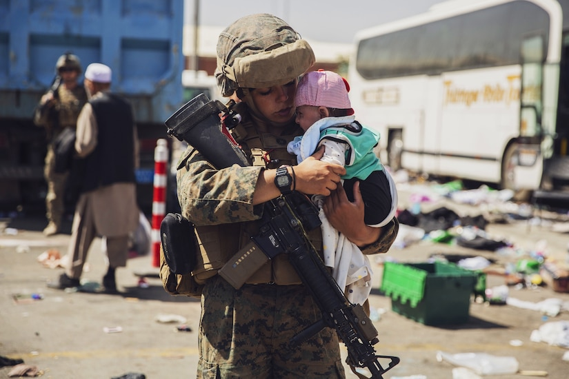 A Marine holds a baby while people file in the background.