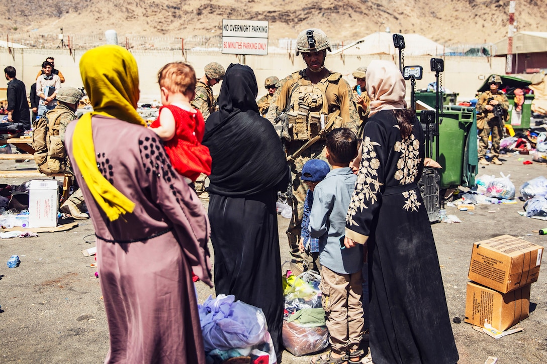 A Marine faces a group of civilians with others in the background.