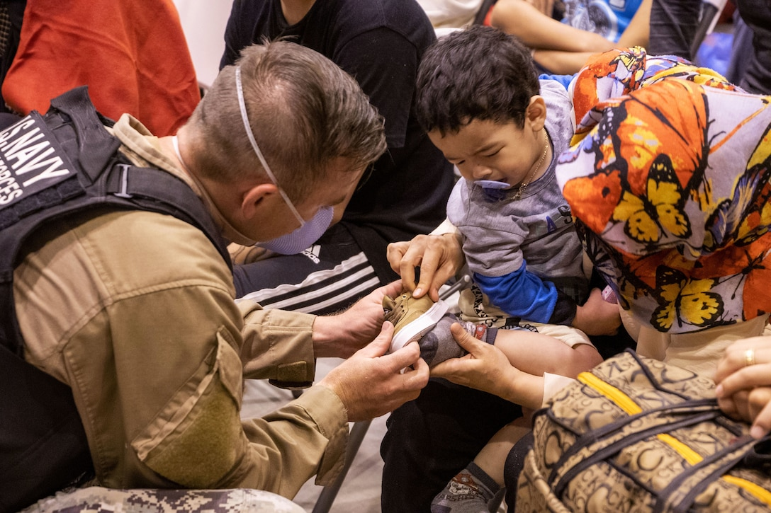A sailor fits a shoe onto a child being held by a civilian.