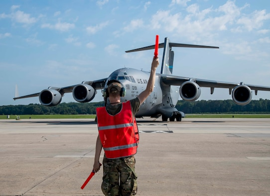 Airman 1st Class Tyler Davis, 736th Aircraft Maintenance Squadron crew chief, prepares to marshal a C-17 Globemaster III at Dover Air Force Base, Delaware, en route to support Afghanistan evacuation efforts, Aug. 24, 2021. Team Dover members donated infant formula, blankets and clothing in support of the safe evacuation of U.S. citizens, Special Immigrant Visa applicants and other vulnerable Afghans. (U.S. Air Force photo by Senior Airman Stephani Barge)