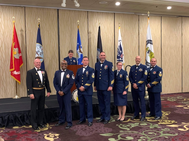 7 people stand in a room in front of flags representing every U.S. branch of service