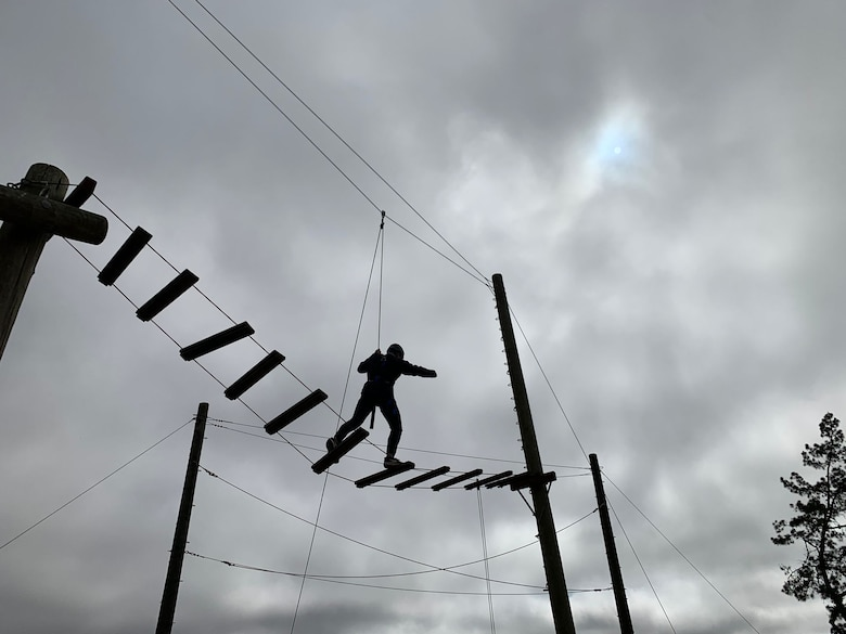 silhouettes are shown of people walking on a rope ladder obstacle course suspended in the air