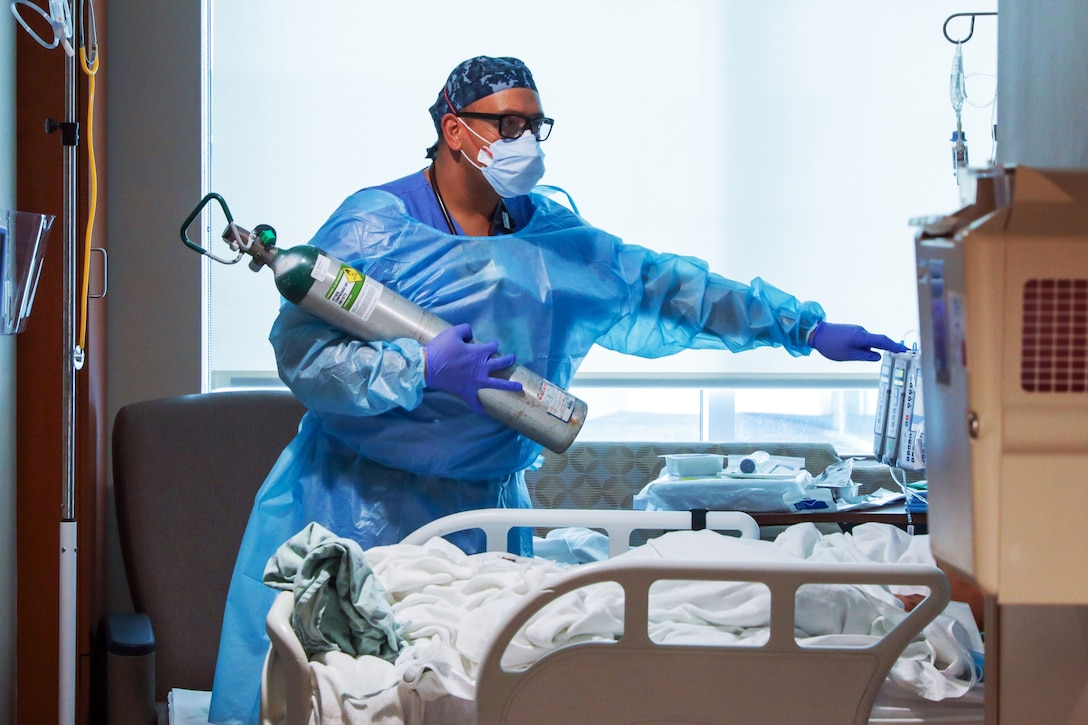 A man wearing a face mask, gloves and medical gown holds an oxygen tank.