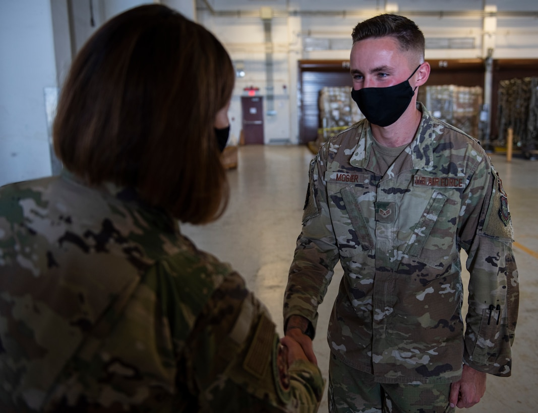 Chief Master Sergeant of the Air Force JoAnne S. Bass coins Senior Airman Cody Mosier, an air terminal operations center information controller assigned to the 734th Air Mobility Squadron at Andersen Air Force Base, Guam, Aug. 27, 2021.