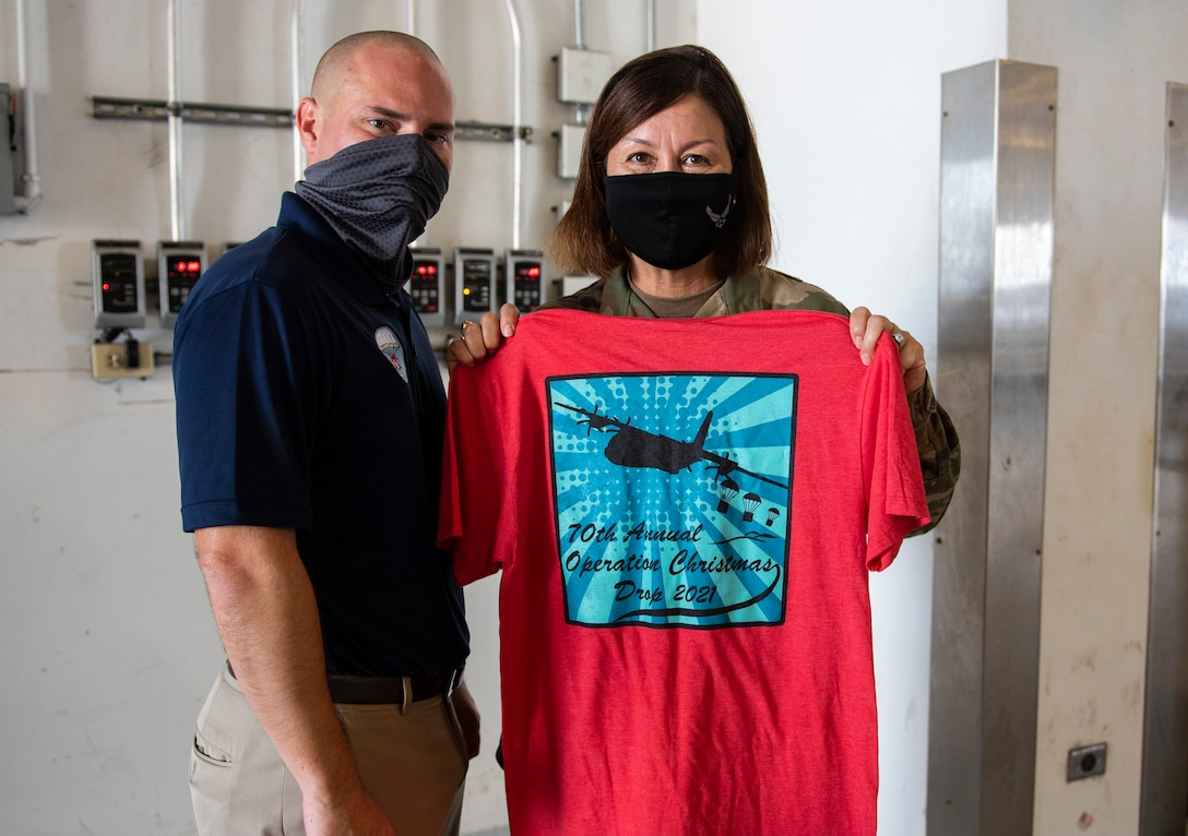 Chief Master Sergeant of the Air Force JoAnne S. Bass receives an Operation Christmas Drop t-shirt from Matthew Carrowan, OCD president, at Andersen Air Force Base, Guam, Aug. 27, 2021.