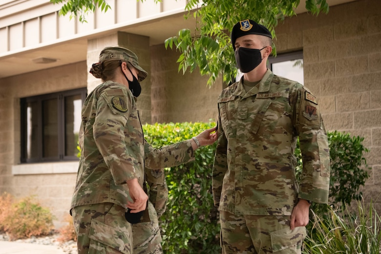 Col. Heather Fox, 9th Reconnaissance Wing commander, left, gives a patch to Airman Samuel Workman, 9th Security Forces Squadron installation entry controller, Aug. 18, 2021, at Beale Air Force Base, California.