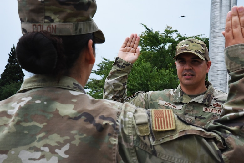 A man in uniform holds his right hand up in a square. A woman in uniform is in the foreground holding her hand up in a square.