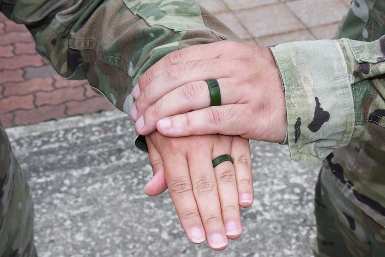 Two hands are shown with matching wedding rings.