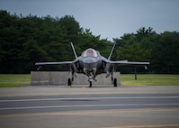 An F-35 sits on pavement. Trees in the background.