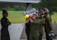 Five Marines hoist a missile to be uploaded to an F-35 fighter jet.