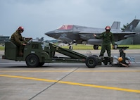 A person drives a weapon lifting machine while another stands nearby.