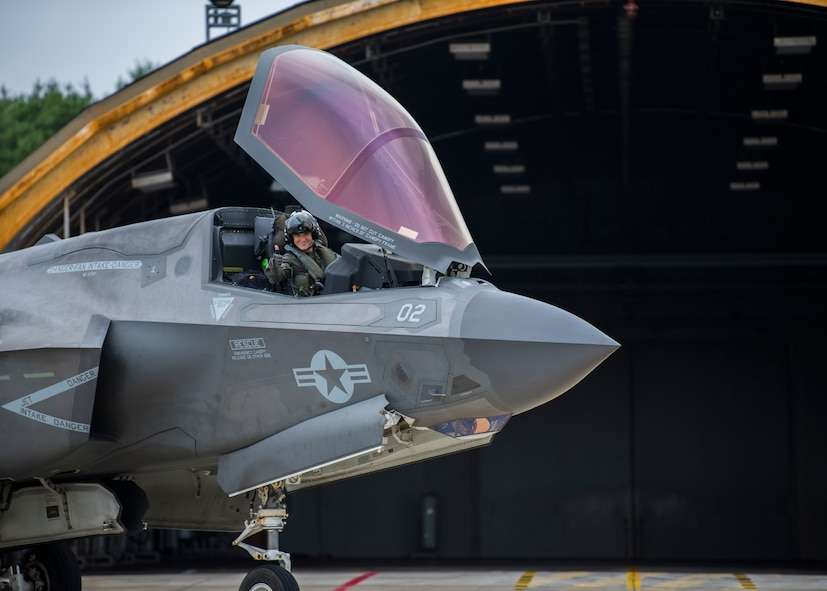 A pilot gives a thumbs-up hand signal from the cokpit of an F-35 sitting in front of a hardened aircraft shelter.