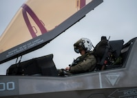 A pilot sits in the cockpit of an F-35. The canopy is open.