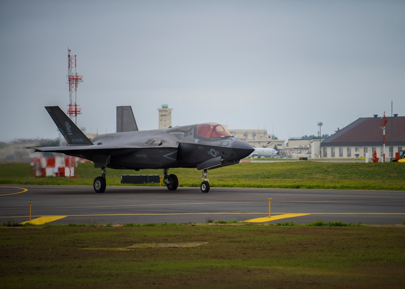 An F-35 taxis from the left.