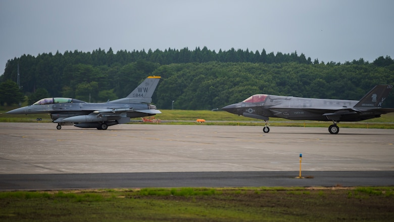 Two fighter jets, an F-16 followed by an F-35, taxi from the right.