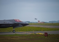 A fighter jet taxis from the left as another takes off from a runway.