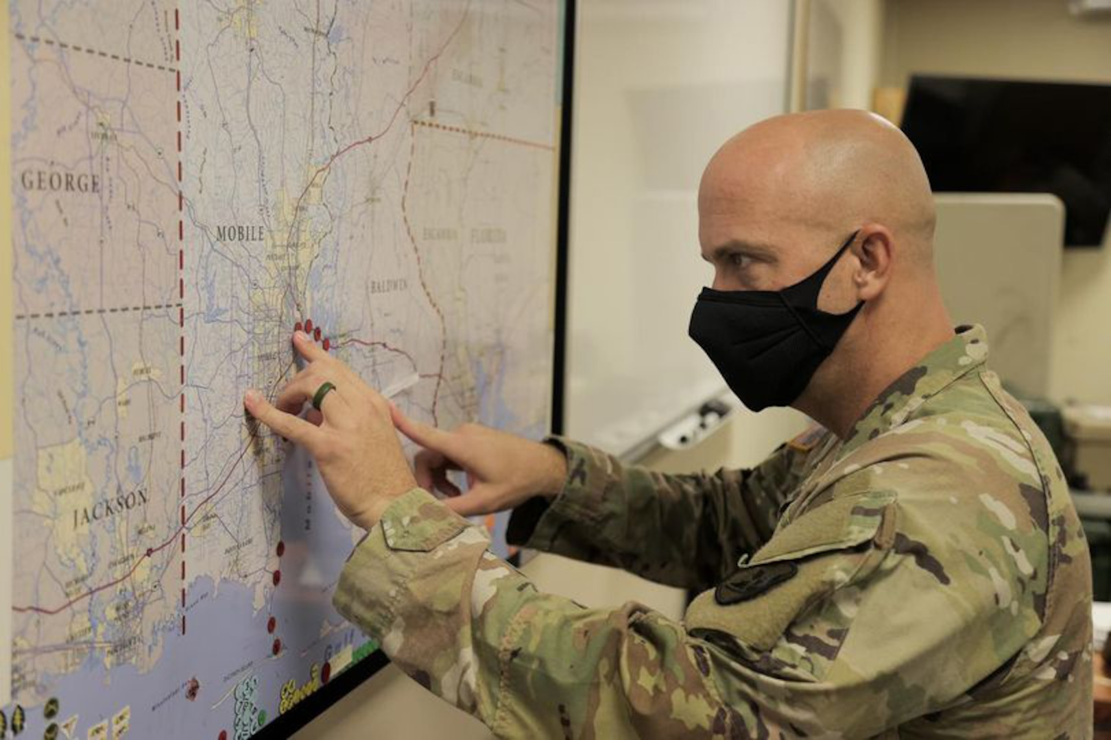 Cpt. Russell Parman of the Alabama National Guard's 711th Combat Sustainment Support Battalion adds dots to a map tracking road closures and incidents due to Hurricane Ida.