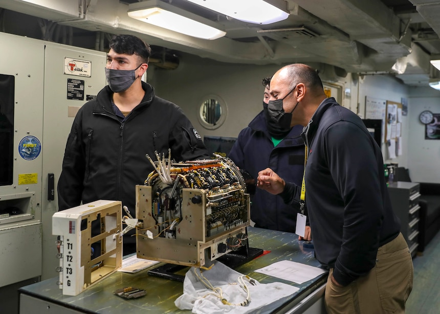 Rep. Jimmy Panetta (right), from California's 20th Congressional District, views an F/A-18 Super Hornet generator control unit aboard the aircraft carrier USS Abraham Lincoln (CVN 72).