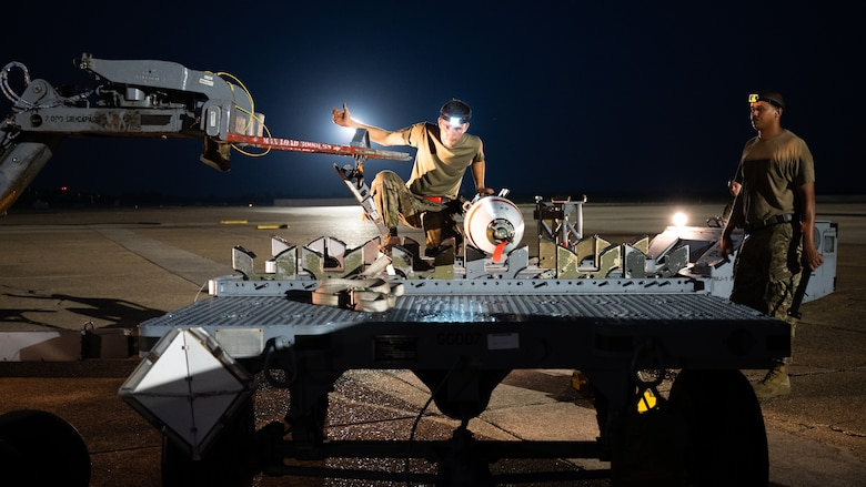 A weapons load crew team from the 2nd Aircraft Maintenance Squadron transfer an Mk-62 Quickstrike naval mine in support of a training exercise at Barksdale Air Force Base, Louisiana, Aug. 25, 2021. The 2nd AMXS weapons load crews have the ability to load naval mines, as well conventional and nuclear weapons. (U.S. Air Force photo by Senior Airman Jacob B. Wrightsman)