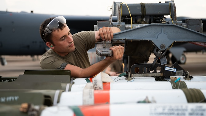 Senior Airman William Oskay, 2nd Aircraft Maintenance Squadron weapons load crew member, prepares to transfer a MK-62 Quickstrike naval mine in support of a training exercise at Barksdale Air Force Base, Louisiana, Aug. 25, 2021. The MK-62 mine is a shallow water aircraft laid mine used primarily against surface and subsurface water craft. (U.S. Air Force photo by Senior Airman Jacob B. Wrightsman)