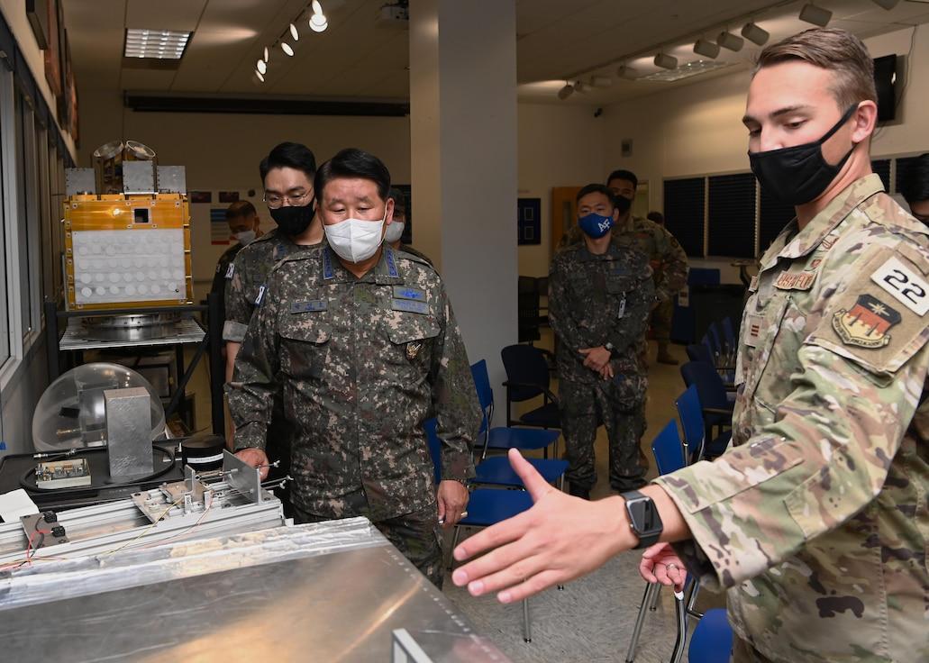 Cadet 1st Class Andrew LaGassa briefs Republic of Korea Air Force Gen. Inho Park, ROKAF Chief of Staff, during a tour of the U.S. Air Force Academy's Astronautics Laboratory