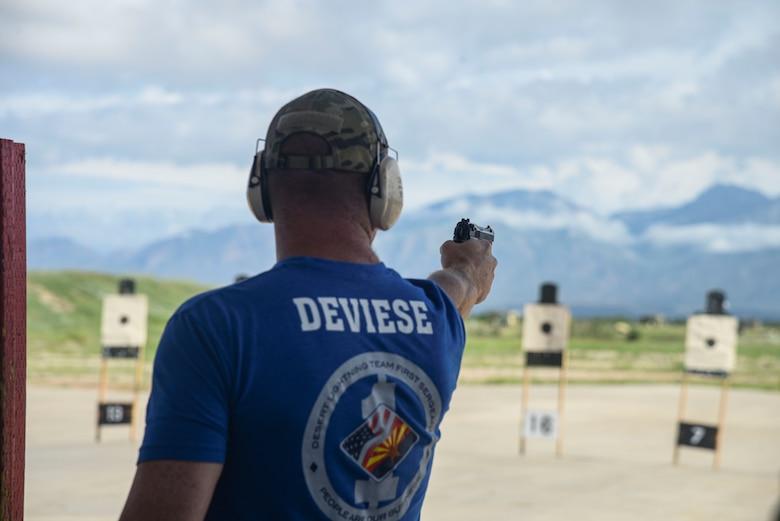 A photo of an Airman firing a pistol at a target.