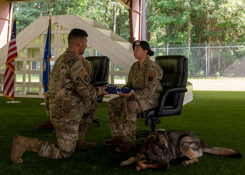 Staff Sgt. Maegan-Ann Baptista, right, 4th Security Forces Squadron military working dog handler, receives a folded American flag from Senior Airman Hector Saenz, 4th Force Support Squadron honor guardsman, during MWD Gina's retirement ceremony at Seymour Johnson Air Force Base, North Carolina, Aug. 26, 2021.