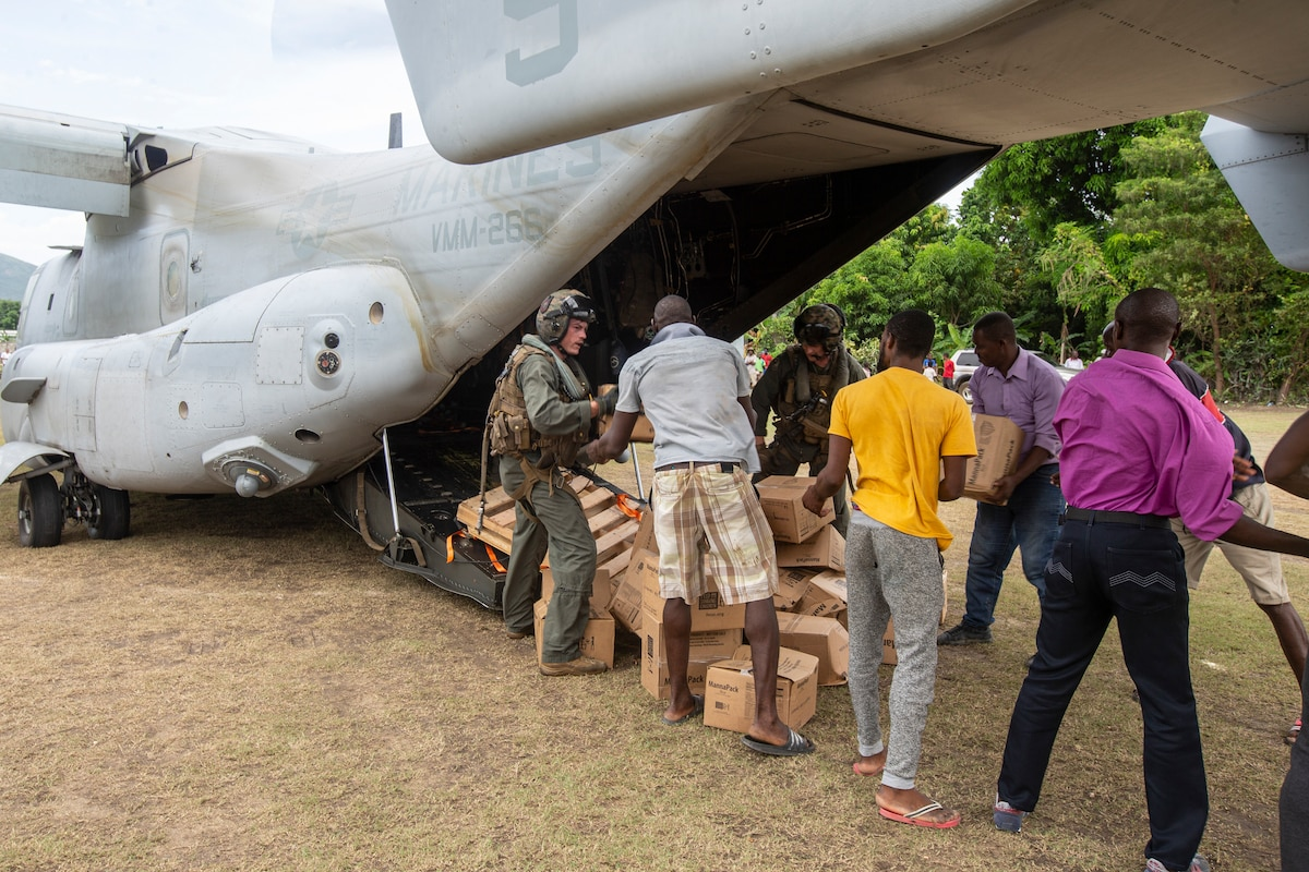 United States Marines with Marine Medium Tiltrotor Squadron 266, 2nd Marine Aircraft Wing, II Marine Expeditionary Force, deliver cases of food in support of Joint Task Force-Haiti for a humanitarian assistance and disaster relief mission in Les Anglais, Haiti, Aug. 27, 2021. (U.S. Marine Corps photo by Cpl. Yuritzy Gomez)