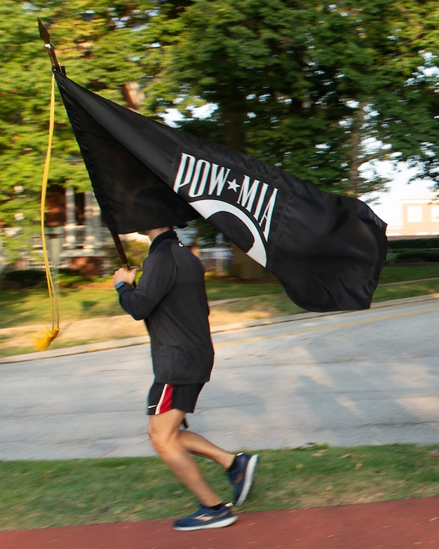 airman running while carrying a POW/MIA flag