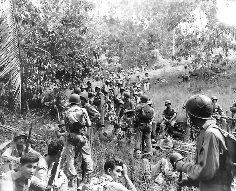Marines rest in a jungle area.