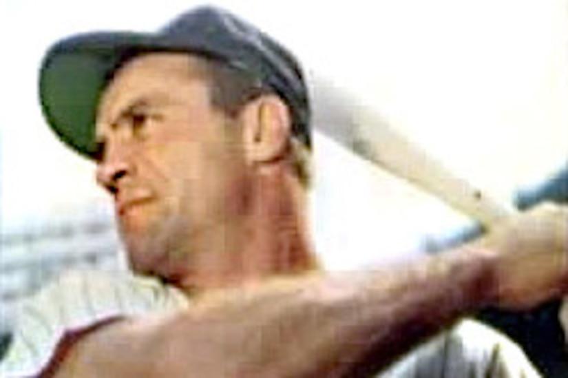 A baseball player holds a bat.