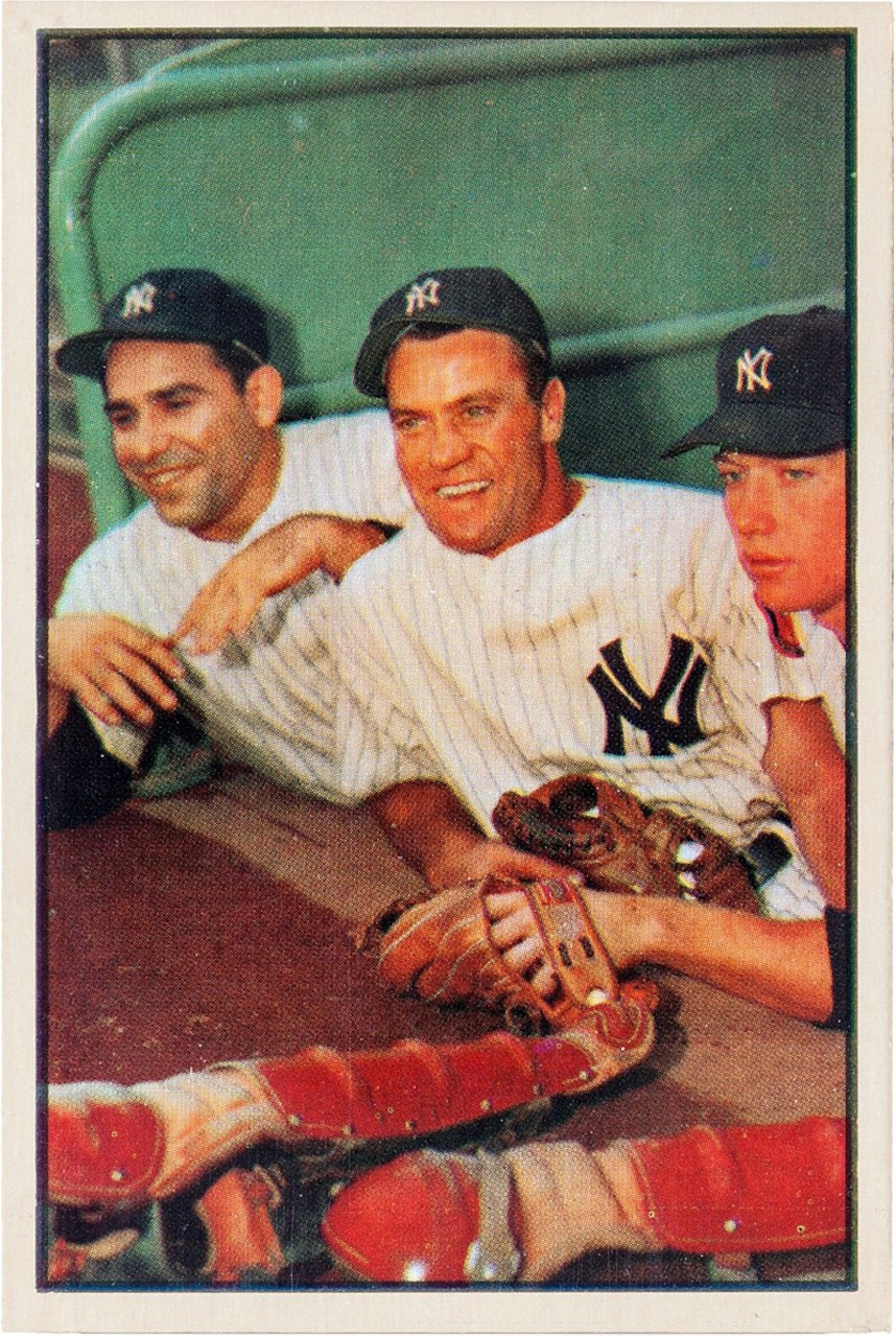 Three baseball players pose for a photo in the dugout.