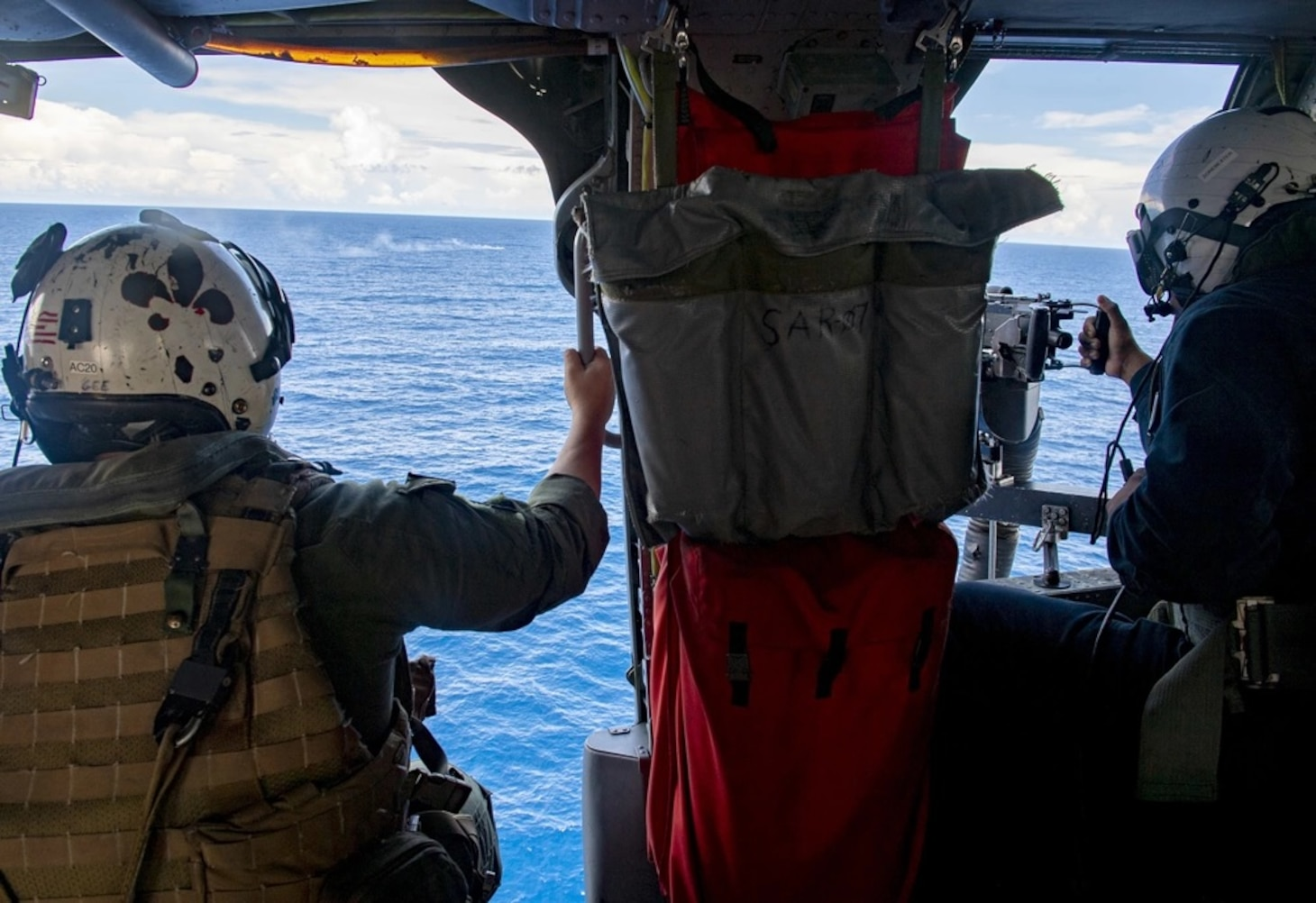 """Naval Aircrewmen (Helicopter) 1st Class Ryan Gee and Mineman Seaman Jonathan Alonsojuarez participate in a gunnery exercise inside of a MH-60S Seahwak helicopter assigned to the """"Blackjacks"""" of Helicopter Sea Combat Squadron (HSC) 21 aboard the Independence-variant littoral combat ship USS Tulsa (LCS 16), Aug. 31, 2021."""
