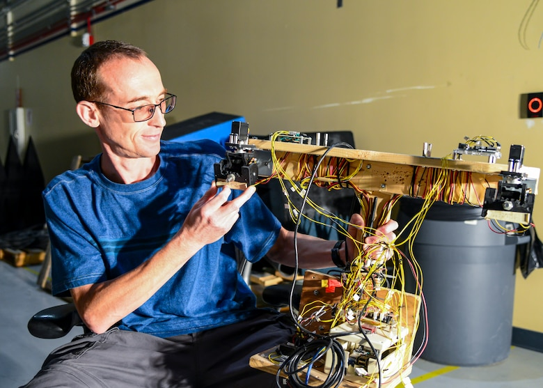 Aleksandr Yarovinskiy explains the workings of a non-flying drone mock-up he built to develop and verify the accuracy of the laser positioning system he designed so a drone would be able to safely and accurately navigate inside the main chamber of the Benefield Anechoic Facility. Yarovinskiy has secured funding from SparkED, the 412th Test Wing's innovation team, to design, build, test and deliver a drone that has the potential to expand and enhance the BAF's data-capture capabilities. (Air Force photo by Gary Hatch)