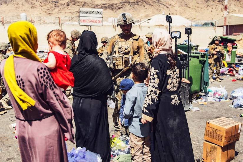 A Marine talks to civilians outdoors.
