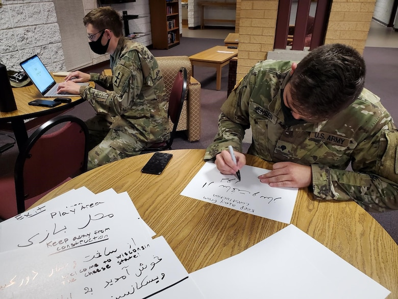 U.S. Army Cpl. Sean Jackett, left, and Spc. Zackary Jensen, Wisconsin Army National Guard linguists, create signs in Dari and Pashto Aug. 25, 2021, to place in a welcome area for Afghans arriving at Volk Field Combat Readiness Training Center near Camp Douglas, Wisconsin. The Department of Defense, through U.S. Northern Command and in support of the Department of State and Department of Homeland Security, is providing transportation, temporary housing, medical screening and general support for up to 50,000 Afghan evacuees.