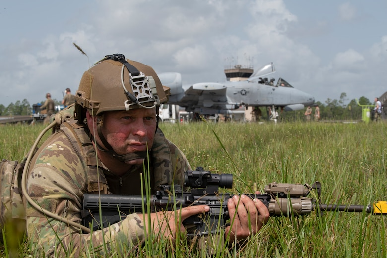 A photo of a man laying on the ground positioned with a weapon for securing the area.