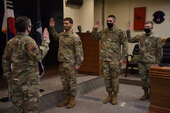 Colonel Jennifer Phelps, 8th Mission Support Group commander, delivers the oath of enlistment to Airman 1st Class Anton Soloshenko, Airman 1st Class Emmanuel Londono, and Airman Nickolai Patchin, in the 8th Fighter Wing conference room at Kunsan Air Base, Republic of Korea, Feb. 1, 2021.