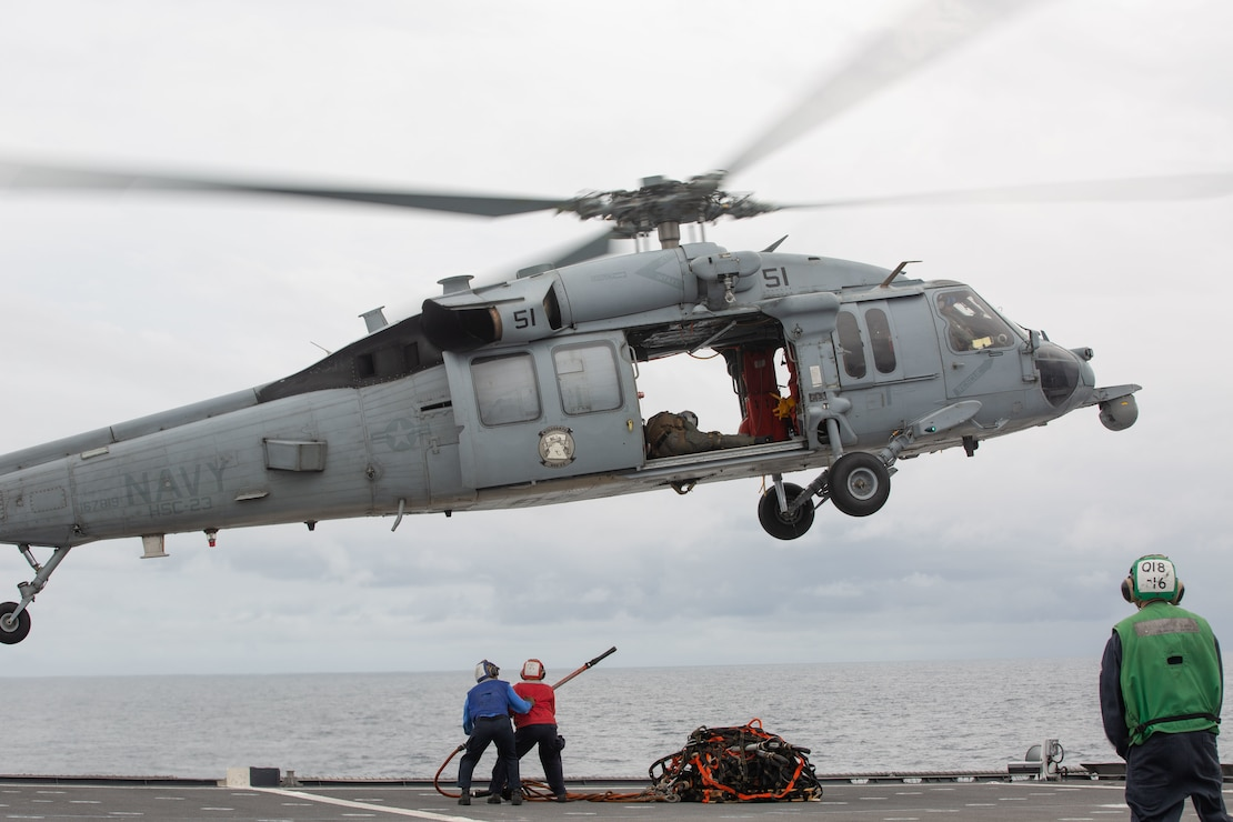 EASTERN PACIFIC OCEAN – Culinary Specialist Seaman Kobe Norfleet and Culinary Specialist 2nd Class Simone Jones, both with the Independence-class littoral combat ship USS Gabrielle Giffords (LCS 10), attach a hook to an MH-60S Sea Hawk during a vertical replenishment on the flight deck of the Gabrielle Giffords Nov. 25, 2020.