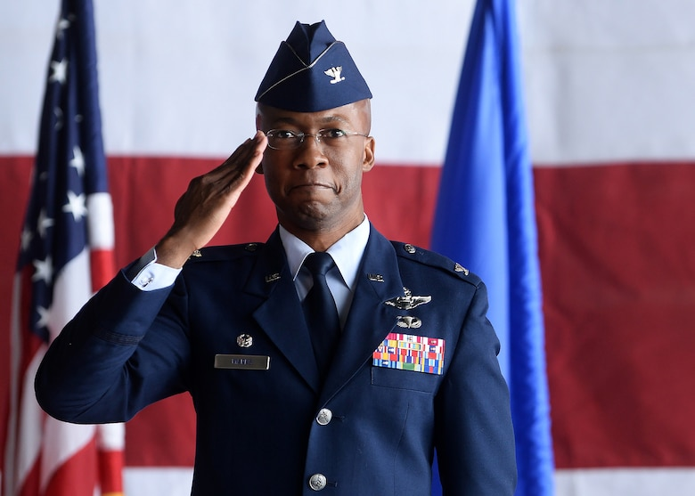 African American man in blue Air Force service dress uniform holds hand in salute position with