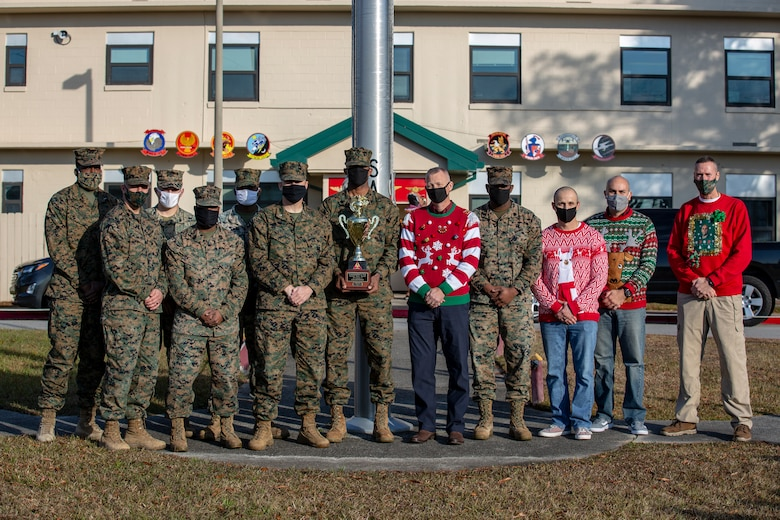 U.S. Marines belonging to Marine Wing Support Squadron 272 pose for a photo with the Commander's Cup at the Marine Aircraft Group 26 headquarters building on Marine Corps Air Station New River, Dec. 18, 2020. Units competed in a series of different sporting events and tournaments, each winning unit was awarded with a Commanders' Cup trophy and monetary compensation in the form of unit and Family Readiness funds. (U.S. Marine Corps Photo by Lance Cpl. Isaiah Gomez)