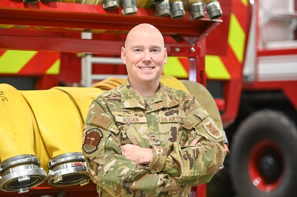 Master Sgt. Luke Rogan stands with his arms folded in front of a fire truck.