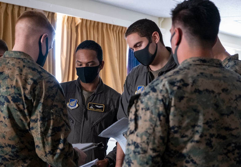 U.S. Air Force Capt. Jay Lambert, center left, and Capt. Bernie Cox, center right, 36th Airlift Squadron C-130J Super Hercules pilots, discuss mission operations for Joint Exercise Littoral Strike at Combined Arms Training Center Camp Fuji, Japan, Jan. 20, 2021.